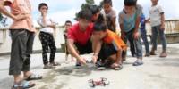 中国の貧困区の子供たちに、大学生がドローンを教える